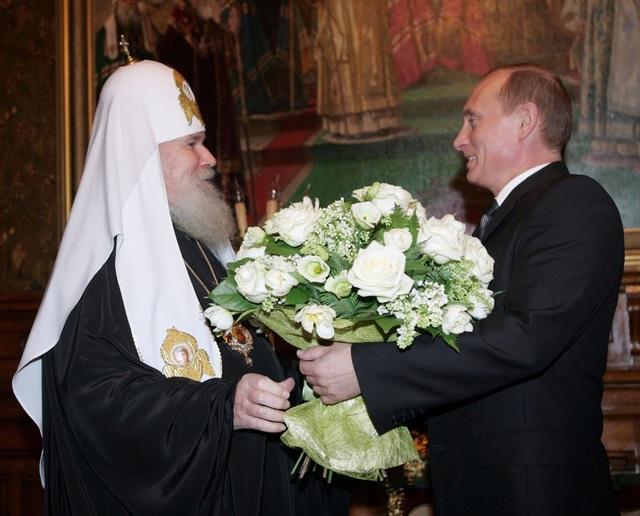 Không chỉ đối với phụ nữ, ông Putin cũng tặng hoa cho những người đàn ông, trong đó có Giáo chủ Nhà thờ chính thống Patriarch Alexy II. (Ảnh: Sputnik)