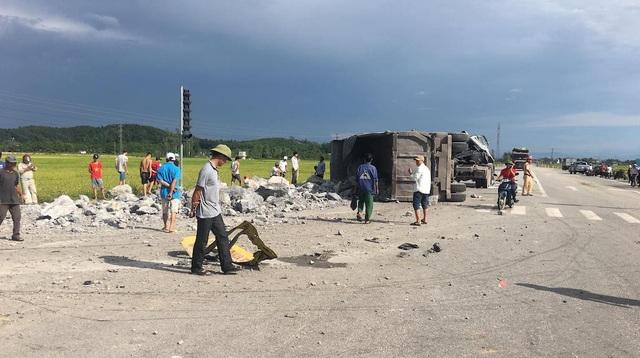 Chiếc xe tải howo chở đá kéo theo rơmooc lật nghiêng và đá trên thùng xe đổ xuống đường.