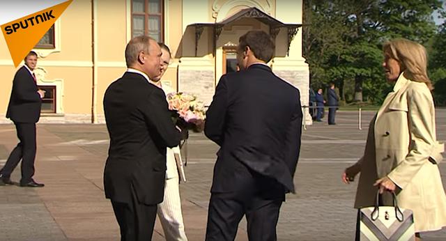 Chào đón Tổng thống Emmanuel Macron và phu nhân ở bên ngoài Cung điện Konstantin ở St Petersburg hôm 24/5, Tổng thống Putin đã tặng Đệ nhất phu nhân Pháp Brigitte Macron một bó hoa màu hồng và vàng.