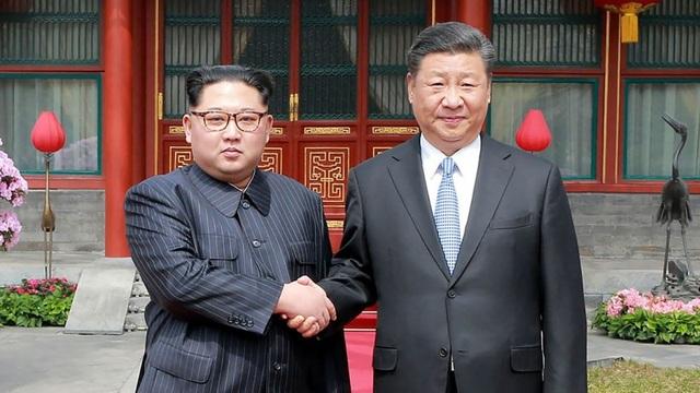 Nhà lãnh đạo Kim Jong-un bắt tay Chủ tịch Tập Cận Bình trong chuyến thăm tới Trung Quốc (Ảnh: Reuters)