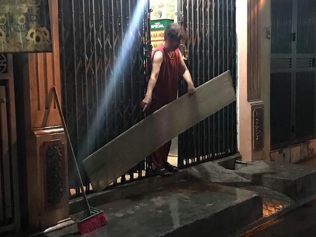 Nhiều người dân dùng cả tấm chắn để ngăn không cho nước vào nhà sau cơn mưa rào gây ngập úng.