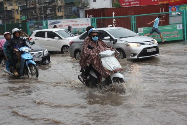 Nhiều người vất vả, hì hục vượt qua dòng nước trên đường.