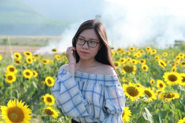 Một thiếu nữ tạo dáng bên hoa hướng dương