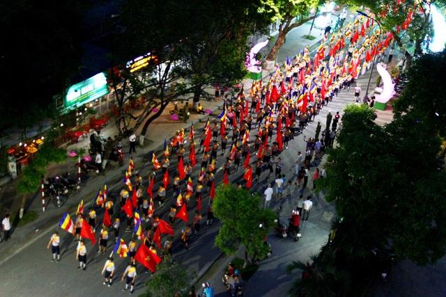 4 hàng dọc mang cờ Tổ quốc và cờ Phật đi sau xe hoa