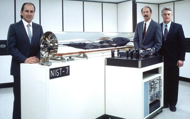 Các nhà nghiên cứu bên cạnh đồng hồ nguyên tử Cesium mã NIST-7. Được đặt tại Gaithersburg, bang Maryland, chiếc đồng hồ này chịu trách nhiệm đo đếm thời gian ở Mỹ từ năm 1993 đến năm 1999, nhưng sau này đã được thay thế bằng loại đồng hồ Cesium khác chính xác hơn. Ảnh: Viện Tiêu chuẩn và Công nghệ Quốc gia Mỹ.