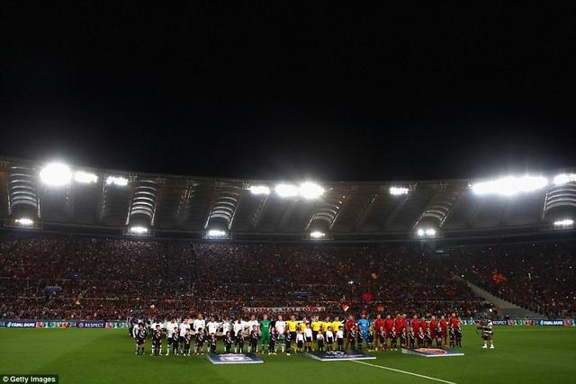 Cầu thủ Liverpool và Roma bước vào trận lượt về trên sân nhà. Liverpool mặc áo trắng, Roma mặc áo đỏ