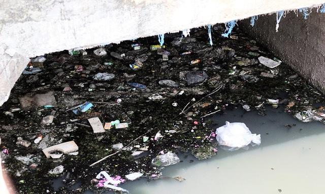 Lòng mương ken đặc đủ loại rác thải do người dân thiếu ý thức vứt xuống.