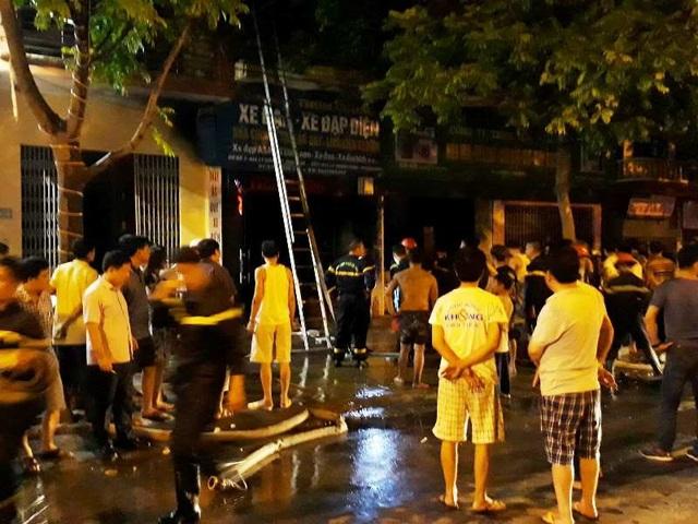 Người dân và lực lượng chức năng nhanh chóng đưa 3 mẹ con trên tầng 2 ngôi nhà bị cháy ra ngoài