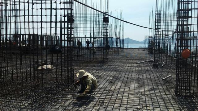 Công nhân đang gấp rút hoàn thiện các công đoạn để kịp tiến độ cất nóc tòa nhà