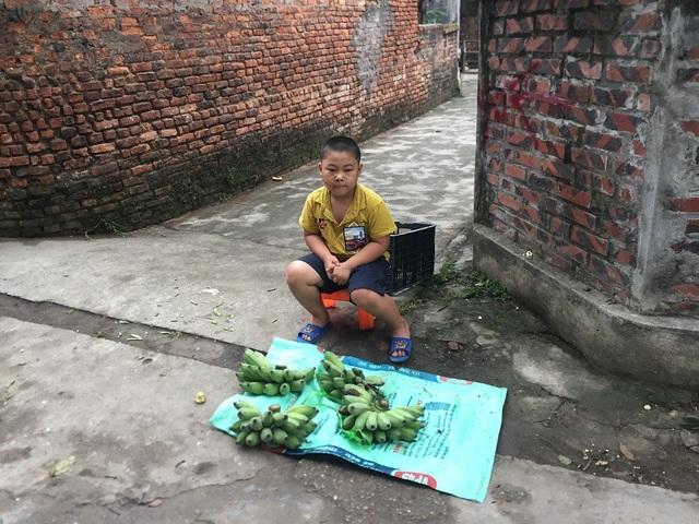 Em còn ngồi trông mấy nải chuối của mẹ mang bán ở ngoài đầu làng.