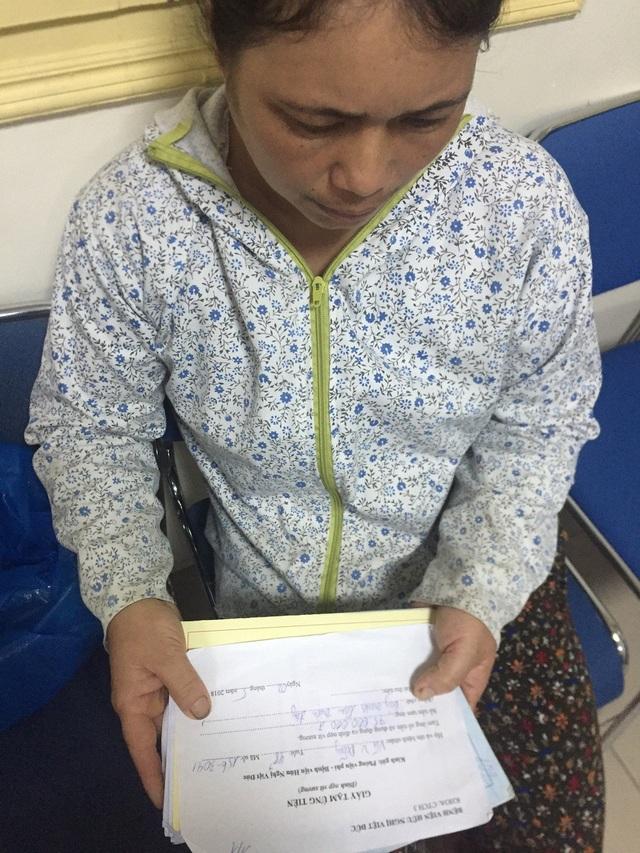 Chị Hà (vợ anh Dũng) bủn rủn tay chân cầm tờ giấy tạm ứng viện phí.