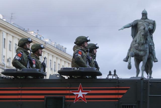 Binh sĩ Nga bồng súng đứng trên xe quân sự tại Moscow.