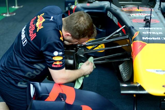 Các nhân viên kỹ thuật chăm sóc chiếc xe đua F1 trước khi chạy ở đường đua mô phỏng.