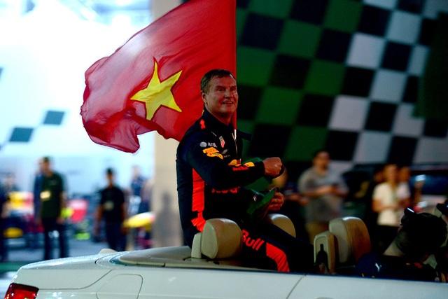 Sau màn trình diễn với chiếc xe đua, cựu tay đua David Coulthard cầm cờ đỏ sang vàng đi chào khán giả.