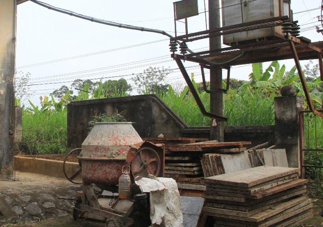 Sân của nhà điều hành trạm bơm được một hộ gia đình trong thôn mượn để tập kết cốt pha và máy trộn bê tông