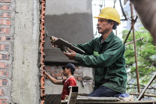 """Bác Ngô Văn Rồng, quê ở Thanh Hóa hiện đang làm thợ hồ ở một công trình trên đường Hồng Hà, Hà Nội chia sẻ: """"Nghề này vất vả mà nguy hiểm thật đấy nhưng vì miếng cơm, manh áo vẫn cứ phải làm thôi, ngót nghét cũng 20 năm rồi""""."""