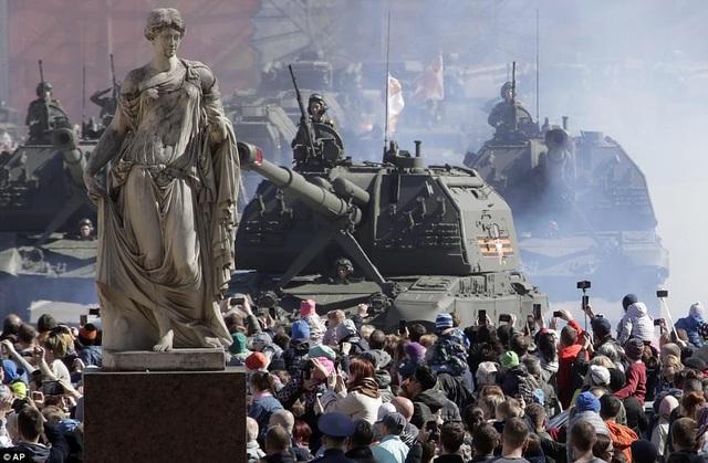 Mặc dù lễ duyệt binh chính thức chưa bắt đầu, nhưng nhiều người Nga đã tập trung tại nơi diễn tập để tận mắt chứng kiến dàn khí tài hùng hậu của quân đội. Trong ảnh: Xe quân sự Nga di chuyển qua Quảng trường Cung điện ở St. Petersburg. (Ảnh: AP)