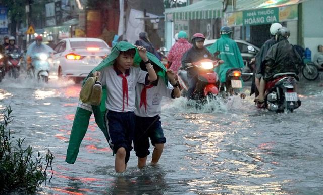 2 học sinh tiểu học che áo mưa dìu nhau qua dòng nước