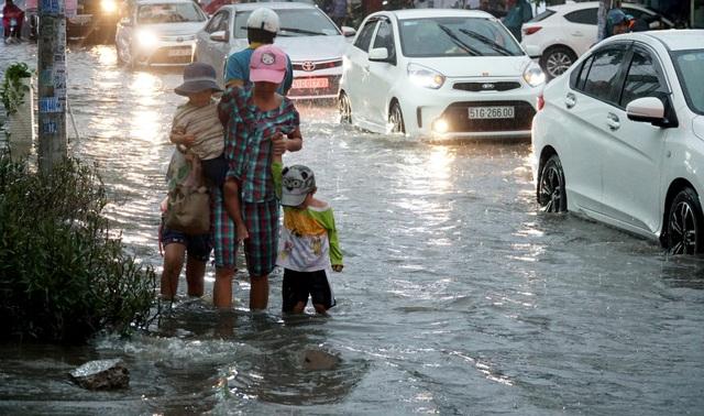 Nhiều phụ huynh dắt con lội nước về nhà sau giờ tan lớp