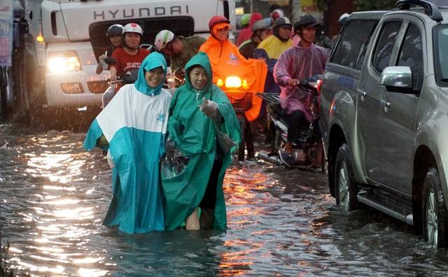 2 phụ nữ lội nước đi bộ dưới đường
