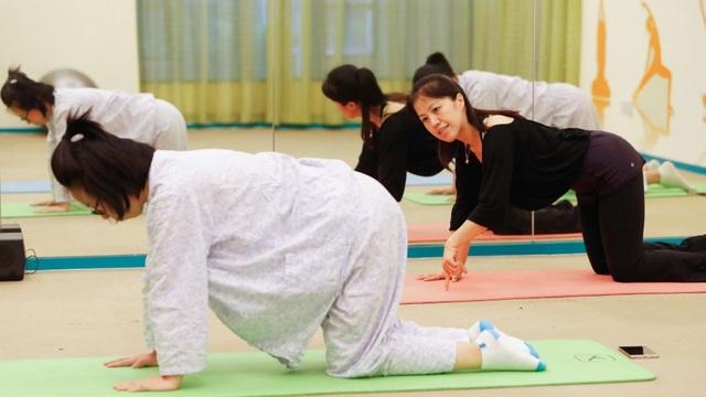 Các bà mẹ trẻ tập yoga với người hướng dẫn tại một trung tâm chăm sóc sau sinh ở Thượng Hải. (Nguồn: AFP)