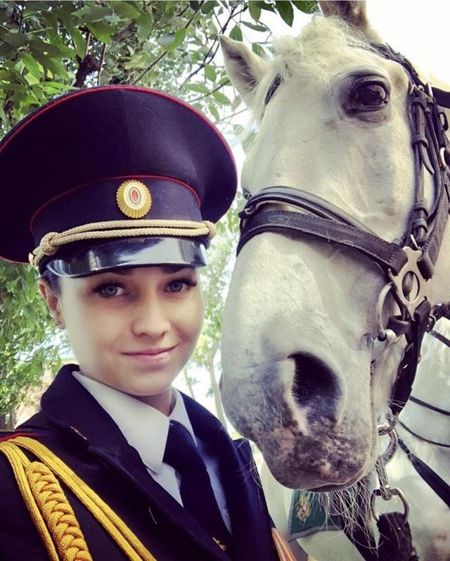 Trước đó. hãng tin RIA Novosti từng phỏng vấn một nữ trung sĩ có tên Tatyana Zima trong một sự kiện đặc biệt về vai trò của phụ nữ trong lực lượng cảnh sát. Cô này có diện mạo khá giống cô gái trong bức ảnh do người dùng SRS@VDV đăng tải. Cô kể rằng đã học cưỡi ngựa từ năm 10 tuổi và quyết tâm trở thành cảnh sát khi vẫn đang ngồi trên ghế nhà trường. Trong ảnh: Cô Tatyana Zima (Ảnh: Twitter)