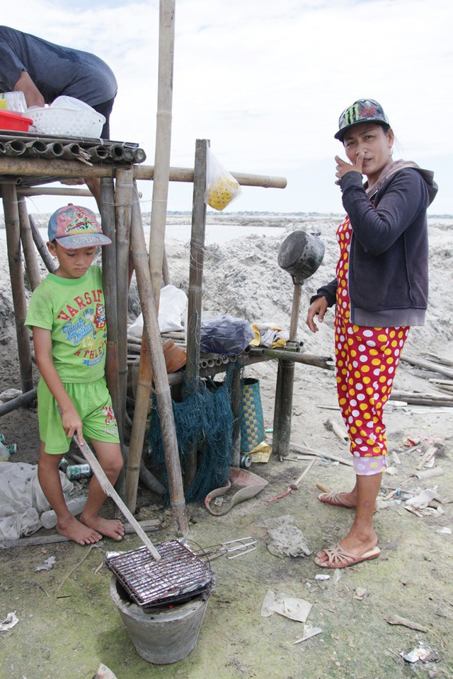 2 mẹ con nhà ngư dân anh Nò ở xã Phú Xuân bắt đầu nướng cá trên giấy bạc