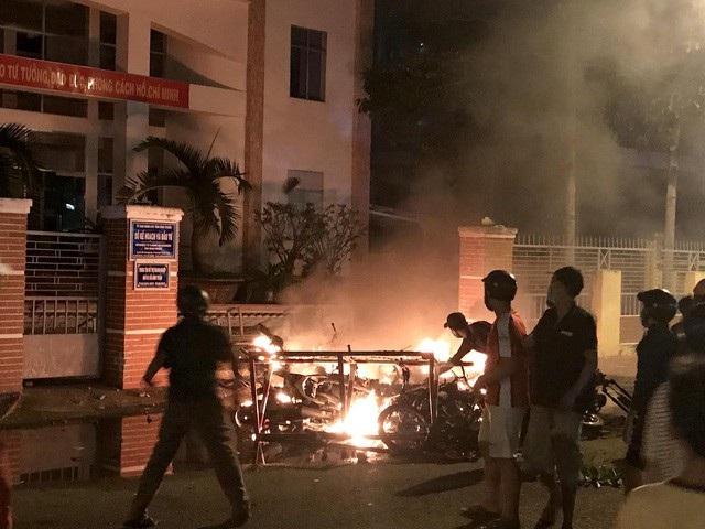 Một số đối tượng quá khích lôi xe máy từ trong Sở Kế hoạch và Đầu tư ra đốt phá. Ảnh: Nguyễn Thanh – TTXVN