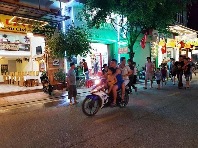Xe máy lưu thông trên phố đi bộ, người điều khiển và người ngồi sau không đội mũ bảo hiểm.