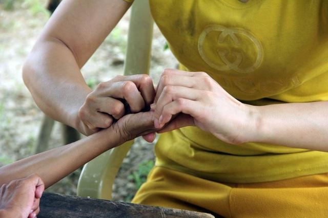 Phải khó khăn lắm người mẹ mới lôi được những ngón tay đã co quắp lại. Người mẹ rớt nước mắt nói, có lẽ trời thương cho nỗ lực của vợ chồng mà chân tay con còn cử động được.