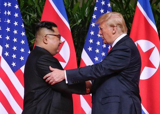 Tổng thống Trump đưa một tay bắt tay ông Kim Jong-un trong khi tay còn lại đặt lên cánh tay nhà lãnh đạo Triều Tiên (Ảnh: EPA)