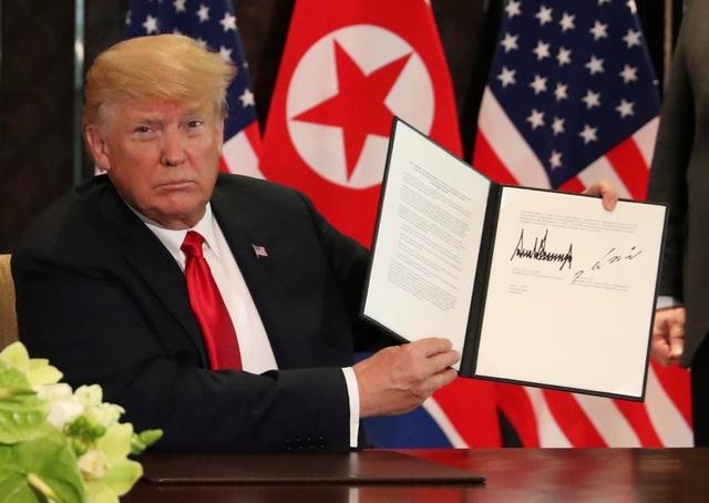 Tổng thống Trump giơ tuyên bố chung Mỹ - Triều sau khi ký kết cùng nhà lãnh đạo Kim Jong-un (Ảnh: Reuters)