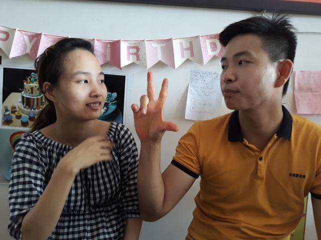 Hai vợ chồng giao tiếp bằng ngôn ngữ cử chỉ, giao tiếp với khách hàng thông qua cây viết và cuốn sổ