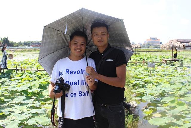 Phó nháy Nguyễn Minh Tiến (phải) mỗi ngày kiếm từ 1,5 - 2 triệu đồng nhờ nghề chụp ảnh cho khách tại đầm sen Hồ Tây.