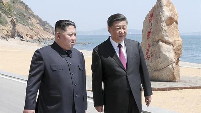 Nhà lãnh đạo Triều Tiên Kim Jong-un và Chủ tịch Trung Quốc Tập Cận Bình trò chuyện khi ông Kim thăm Trung Quốc lần 2 hồi tháng 5. (Ảnh: Reuters)