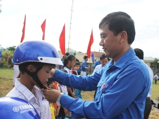 Bí thứ Tỉnh đoàn Bình Định Nguyễn Xuân Vĩnh tặng mũ bảo hiểm cho học sinh.