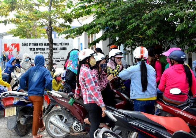 Các công nhân đình công tụ tập trước cổng của công ty