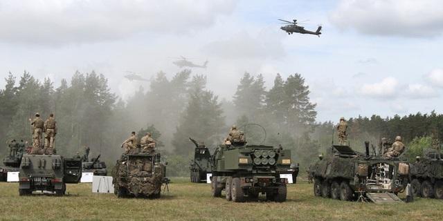 Saber Strike 2018 là cuộc tập trận đa quốc gia do Mỹ dẫn đầu, được tổ chức từ ngày 3-15/6 tại nhiều quốc gia Đông Âu và Baltic. Trong ảnh: Các binh sĩ ngồi trên xe quân sự tham gia cuộc tập trận Saber Strike 2018 tại thao trường Bemowo Piskie, Ba Lan ngày 15/6.