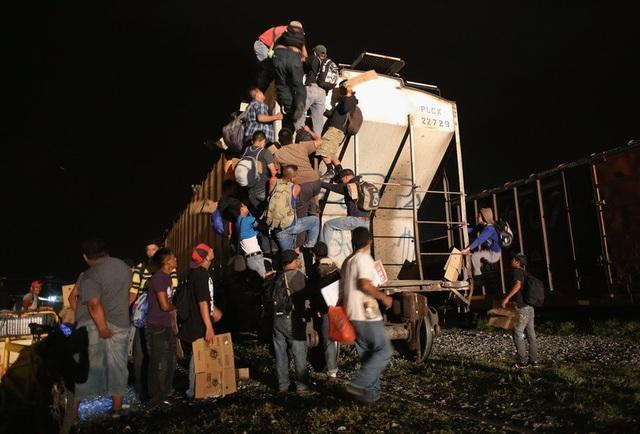Một trong những tác phẩm của John Moore chụp lại cảnh những người tỵ nạn vượt thoát khỏi hàng rào biên giới để đoàn tụ với gia đình.