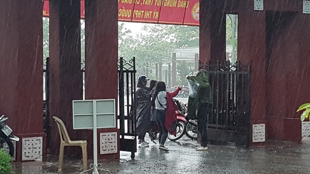 Những chiếc áo mưa đưa cho thí sinh để các em trùm vào người chạy vào phòng thi