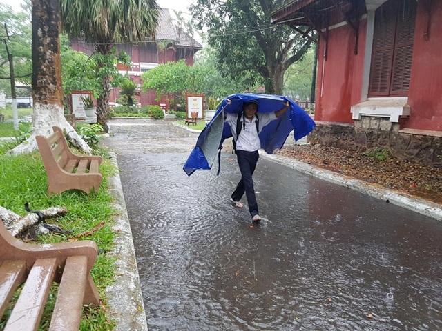 Một thí sinh tự mình đi vào phòng thi sau khi có chiếc áo mưa