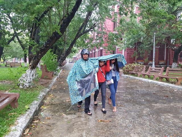 Bố đưa con đi dự thi trong mưa