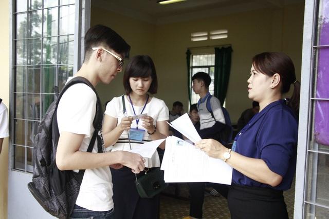 Giám thị đối chiếu thí sinh với chứng minh nhân dân trước khi vào phòng. (Ảnh: Thúy Diễm)