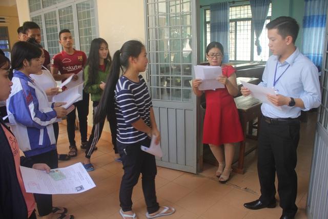 Các thi sinh kiểm tra lại giấy báo dự thi. (Ảnh: Phạm Hoàng)