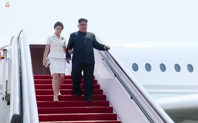Nhà lãnh đạo Kim Jong-un và phu nhân khoác tay nhau bước xuống chuyên cơ bắt đầu chuyến thăm Trung Quốc lần ba. (Ảnh: Yonhap)