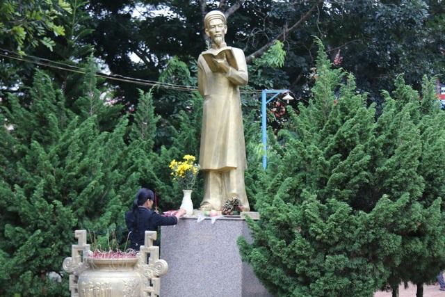 Phụ huynh và thí sinh tranh thủ cầu may trước tượng đài nhà giáo Chu Văn An Tại điểm thi Trường THPT Chu Văn An (TX. Gia Nghĩa, Đắk Nông). (Ảnh: Dương Phong)