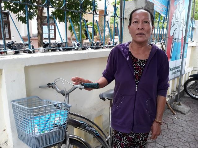 Bà Phạm Thị Thảo sát cánh cùng con đến điểm thi trường THPT Trần Quốc Tuấn (TP. Quảng Ngãi) trên chiếc xe đạp. (Ảnh: Quốc Triều)