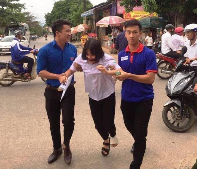 Tình nguyện viên giúp đỡ thí sinh bị đau chân tại điểm thi THPT Vĩnh Linh (Ảnh: Thu Hà)