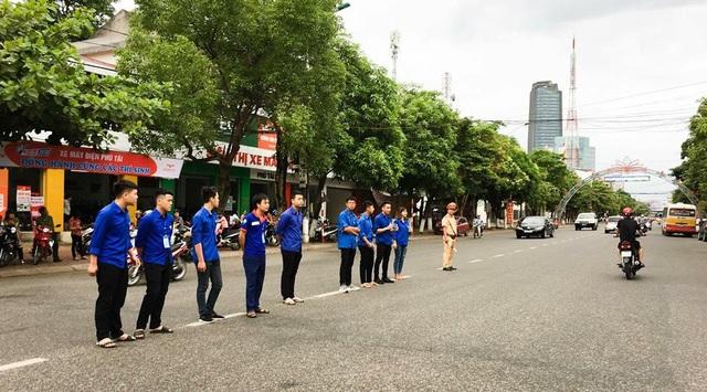 Các bạn tình nguyện hỗ trợ các lực lượng chức năng tạo thành một hàng rào để phân luồng giao thông, đảm bảo an toàn cho các thí sinh đến dự thi