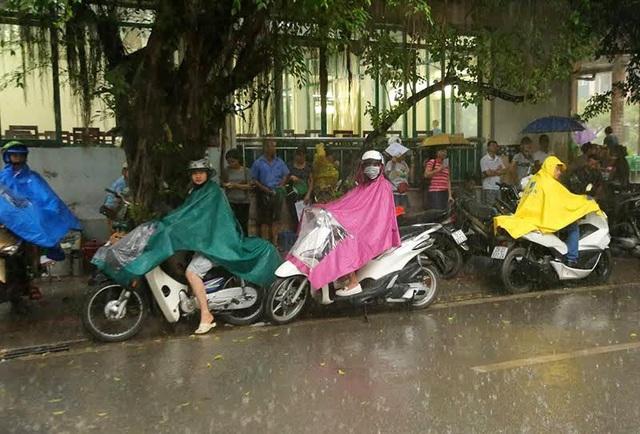 Phụ huynh tại Hà Nội đứng trong mưa đợi con thi buổi cuối, kỳ thi THPT quốc gia 2018. (Ảnh: Mai Châm)
